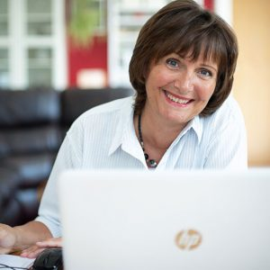 Marian Timms at her computer smiling towards camera